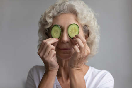 Head shot close up elderly woman hold two cucumbers slices cover eyes enjoy home spa beauty treatment procedure, superior natural skin and body cosmetics eco products for aged skin, skincare concept