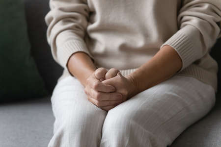 Close up image elderly woman feels nervous anxious or lonely put clenched hands on laps sitting on couch indoors. Older patient of nursing home, senile diseases and geriatric, declining years concept 版權商用圖片