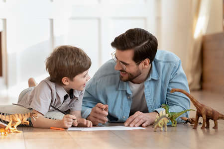 Happy small boy lying on floor with caring dad, enjoying funny conversation, discussing hand drawn pictures in living room. Emotional positive father involved in funny domestic activity with son.
