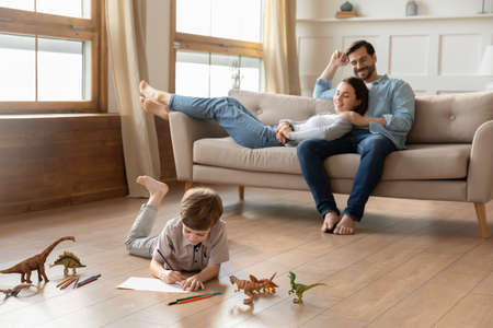 Smiling loving young bonding couple parents relaxing on comfortable sofa, watching little kid son drawing pictures in album, lying on wooden floor in living room, happy family weekend pastime.