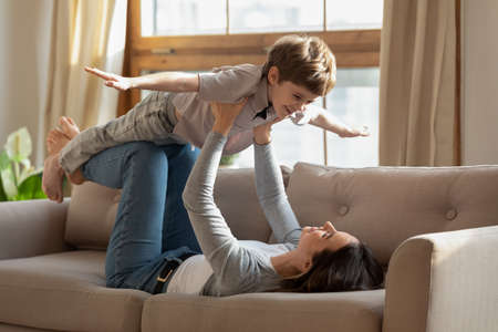 Happy excited little child boy pretending to be airplane, having fun with caring mommy on sofa. Strong young mother enjoying free weekend playtime with energetic son in living room, childcare concept.