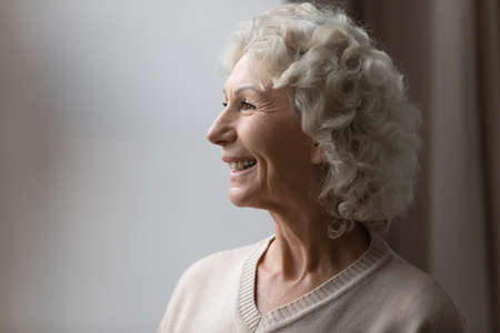 Old woman smile admire view from window look at distance enjoy new carefree day retired life. Dentistry service for older generation people, pension home, medical insurance for senior citizens concept