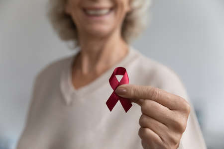 Close up aged female show to camera red ribbon symbol, substance-abuse prevention, solidarity of people living with HIV awareness fight against AIDS. World AIDS Day. Health check up promotion concept