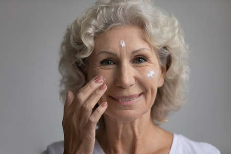 Close up face elderly happy attractive woman, 65s grey haired female smiling looking at camera feels satisfied applies moisturizer facial cream serum for senior skin, age defense treatment ad concept