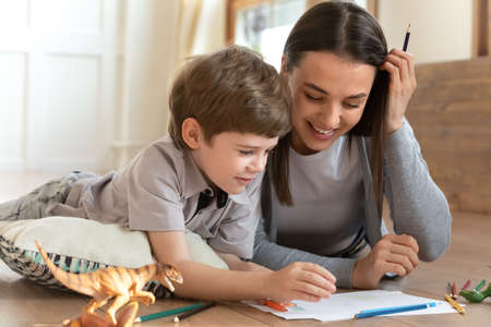 Adorable happy little child boy hand drawing pictures in paper album with loving mommy, lying together on floor. Smiling female babysitter enjoying daycare pastime with small kid in living room. 版權商用圖片