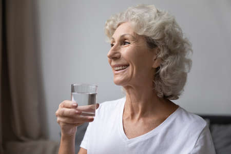 Smiling elderly woman holding glass of still fresh pure distilled water enjoy good life habit, after awakening morning routine for skin body health care and longevity, healthy lifestyle, diet concept