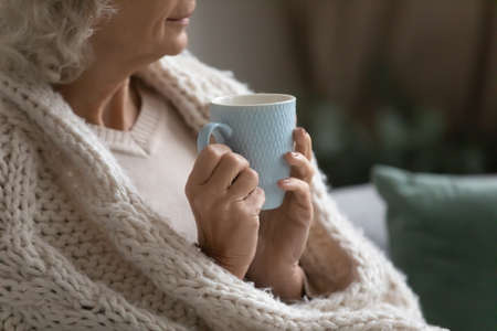 Aged calm woman resting wrapped in knitted plaid drink evening tea look into distance, close up. Old grey haired lady covered in warm cozy cardigan enjoy morning coffee spend lazy time at home concept