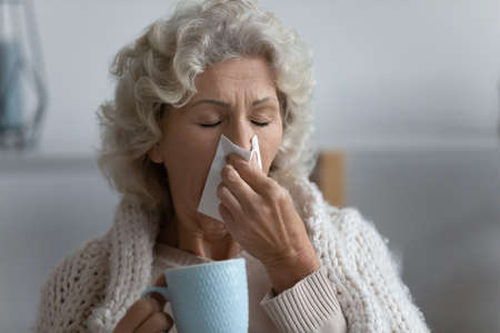 Close up unhealthy elderly senior woman caught a cold covered in warm knitted plaid use tissue wiping sneezing blowing runny nose. Sick granny treated at home holds cup takes drinks antiviral beverage
