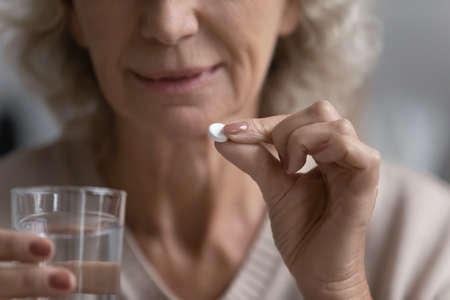 Elderly woman hold white round pill and glass of natural water close up image. Senior female taking medication for aging-associated senile diseases prevention, such as dementia atherosclerosis concept 版權商用圖片