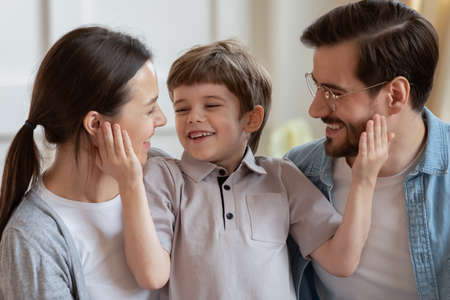 Joyful small cute child boy having fun with happy young parents, spending free time together indoors. Smiling married couple playing with little kid son, enjoying playtime, laughing joking at home.