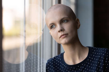 Pensive young ill hairless female patient struggle with oncology look in distance dream think, Caucasian sick woman with cancer feel lonely at home, believe in future recovery, healthcare concept