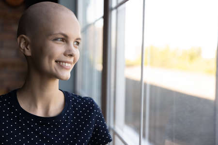 Smiling young Caucasian sick hairless woman suffer from cancer look in distance window dream of recovery, happy ill bald female oncology patient feel hopeful optimistic of future, healthcare concept