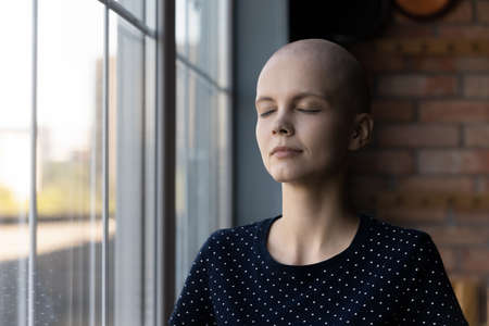 Calm young Caucasian sick hairless woman suffer from cancer meditate relieve negative emotions, relaxed ill bald female patient with oncology feel mindful peaceful, stress free, faith concept 版權商用圖片