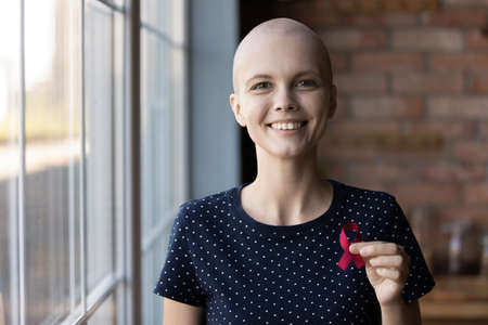 Portrait of smiling sick young Caucasian woman beat breast cancer show red ribbon symbol of disease, happy ill female oncology patient support people with illness, healthcare, recovery concept Reklamní fotografie
