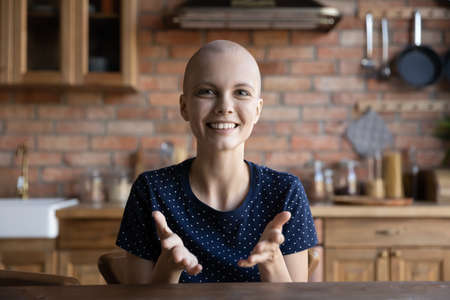 Headshot picture portrait of smiling young Caucasian sick woman blogger shoot online live broadcast vlog, happy ill hairless female patient with cancer oncology feel optimistic talk on video call