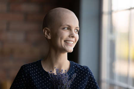 Smiling young sick Caucasian hairless woman look in distance dreaming disease recovery, happy female patient beat cancer, recovered from oncology, feel hopeful optimistic, healthcare concept 版權商用圖片