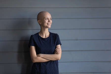 Happy young sick hairless woman with oncology isolated on wooden background look in distance dreaming, smiling ill bald female patient struggling with cancer, feel hopeful optimistic of recovery