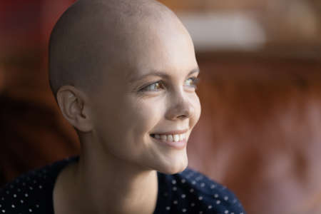 Close up of happy millennial sick hairless woman with oncology look in distance dreaming of illness recovery, smiling young Caucasian ill female patient suffer from cancer feel optimistic hopeful