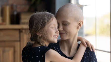 Happy young Caucasian cancer patient sick mother and little daughter hug show love and care, supportive small girl child embrace caress ill hairless mom suffer from oncology, feel grateful thankful