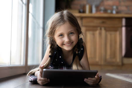 Portrait of cute smiling Caucasian little girl lying on warm floor at home using modern tablet gadget, happy small child kid have fun relax playing application game on pad, study on device online 版權商用圖片