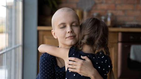Sick young Caucasian cancer patient bald hairless mother hug embrace cute little daughter showing love care, small girl child cuddle support caress ill mom suffering from oncology, gratitude concept