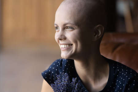 Close up of smiling young sick bald hairless woman suffer from oncology look in distance dreaming thinking of recovery, happy millennial ill female patient with cancer show strength and optimism