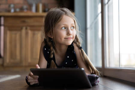 Happy little Caucasian girl lying on warm floor at home use modern tablet gadget look in window dreaming, smiling small child kid have fun relax play on pad device, entertainment, technology concept 版權商用圖片