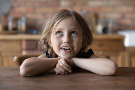 Cute small preschooler blue-eyed girl with braids sit at table in kitchen have fun singing waiting for food, overjoyed little child kid relax at counter, enjoy happy childhood in house or home