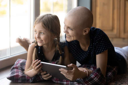 Happy young Caucasian sick cancer patient bald hairless mom and little daughter rest on floor use tablet look in window distance dreaming, smiling ill mother and small girl child relax with pad gadget