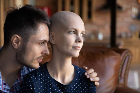 Loving young Caucasian husband hug support sick cancer patient hairless wife, look in distance dream or recovery together, caring man embrace caress woman suffer from oncology, healthcare concept 版權商用圖片