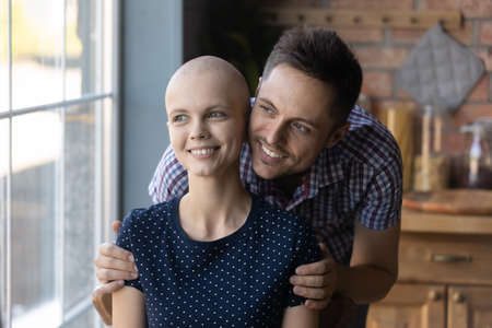 Loving young Caucasian husband hug comfort optimistic sick cancer patient wife, look in distance dream of happy future recovery together, caring man embrace support ill woman, oncology concept 版權商用圖片