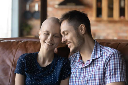 Caring young Caucasian man sit on couch hug comfort sick cancer patient hairless wife, happy husband support caress embrace ill woman suffer from oncology, show love gratitude, healthcare concept 版權商用圖片
