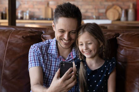 Happy young Caucasian father and small daughter sit relax on couch at home watch funny video on smartphone gadget together, smiling dad and little girl child using modern cellphone device at home 版權商用圖片