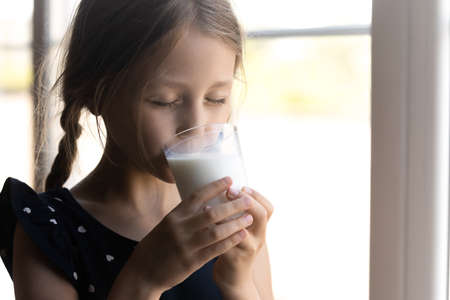 Cute little Caucasians girl drink tasty nutritional milk from glass, get vitamins and calcium, small preschooler kid child enjoy delicious organic grain healthy yoghurt at home, healthcare concept