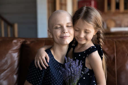 Happy young Caucasian ill cancer patient mom and little daughter hug embrace show gratitude and love, cute small girl child present flowers bouquet to sick bald hairless mother, support and care
