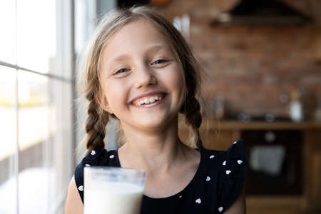 Close up headshot portrait of happy little preschooler girl with white moustache from drinking tasty nutritional milk, smiling small child kid laugh taste delicious organic lactose free yoghurt