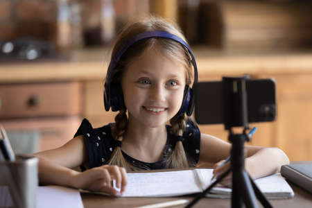 Smiling small girl sit at table handwrite in notebook study at home record video tutorial lesson on smartphone, smart little child have online class on cell, do homework, distant education concept