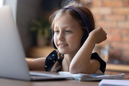 Close up of smiling small girl in headphones look at laptop screen prepare homework assignment on gadget, happy smart little child study online on computer device at home, distant education concept
