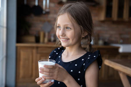 Smiling small Caucasians girl child look in distance drink milk from glass, get protein calcium vitamins, little preschooler kid enjoy delicious tasty nutritional organic healthy grain yoghurt at home