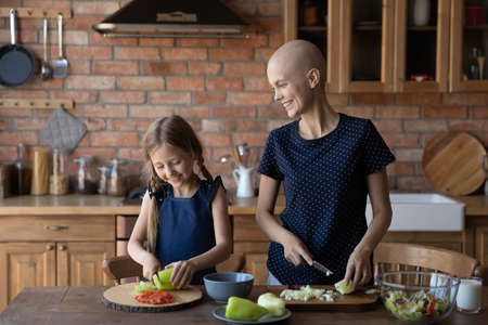 Smiling young sick cancer patient bald hairless mom and little daughter cooking together at home kitchen, happy ill mother and small girl child make healthy diet food together, vegetarian concept 版權商用圖片