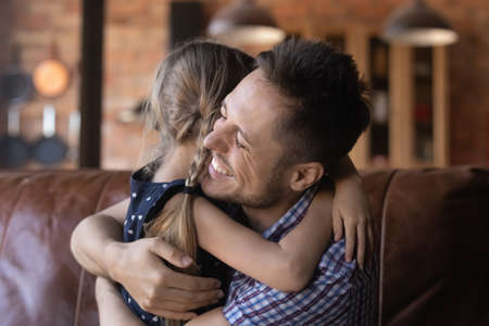 Happy young Caucasian dad and little daughter hug cuddle make peace reconcile after fight, smiling father and small girl child embrace show love and gratitude, feel thankful grateful at home