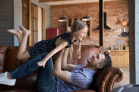Happy young Caucasian father lying on couch play with overjoyed small daughter at home kitchen studio, smiling dad hold in arms imitate plane fly with excited little girl child, have fun together 版權商用圖片