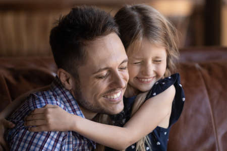 Cute little Caucasian girl child hug happy young father show love and gratitude, smiling small daughter embrace caress excited dad, demonstrate care and affection, enjoy time play at home together