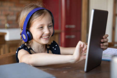 Overjoyed little Caucasian girl sit at table in kitchen have fun watching video on modern tablet gadget, happy small child laugh smile browse internet on pad at home, children and technology concept