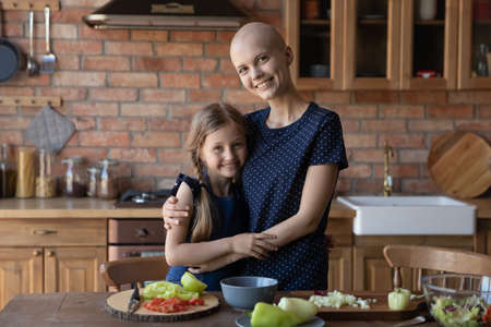 Portrait of happy young Caucasian sick cancer patient mother and small daughter cook together at home kitchen, smiling ill hairless mom and little girl child hug embrace make healthy diet food