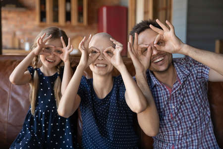 Portrait of overjoyed young family with little kid with sick cancer patient mother make funny faces relax at home together, happy man support ill hairless wife feel playful with small daughter child
