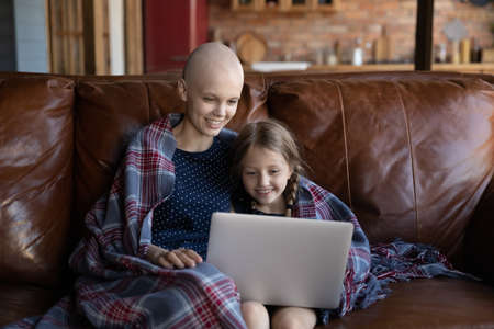 Smiling young Caucasian cancer sick patient mother and small daughter rest on sofa at home watch video on laptop together, happy ill hairless mom and little girl child relax on couch with computer 版權商用圖片
