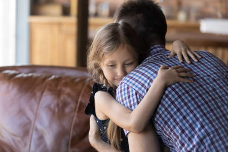 Cute little Caucasian girl hug young father show love and affection, feel grateful thankful, small daughter embrace dad at home, make peace reconcile after family fight, gratitude, bonding concept 版權商用圖片