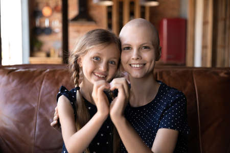 Portrait of smiling young sick of cancer bald mom and little daughter hug show heart love sign gesture with hands, happy hopeful ill hairless mother patient with small girl child, healthcare concept