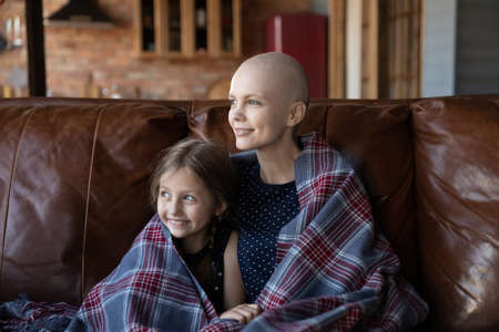 Happy young Caucasian sick cancer patient mom and little daughter sit relax on couch look in distance dream visualize, smiling hopeful ill hairless mother and small girl rest at home enjoy weekend 版權商用圖片
